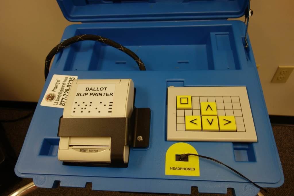 Audio voting machines like this help voters who have poor vision, or who have difficulty reading a ballot or operating the ballot marking systems. It speaks the ballot, choices are entered using the yellow buttons, and the printer puts out a marked ballot slip.