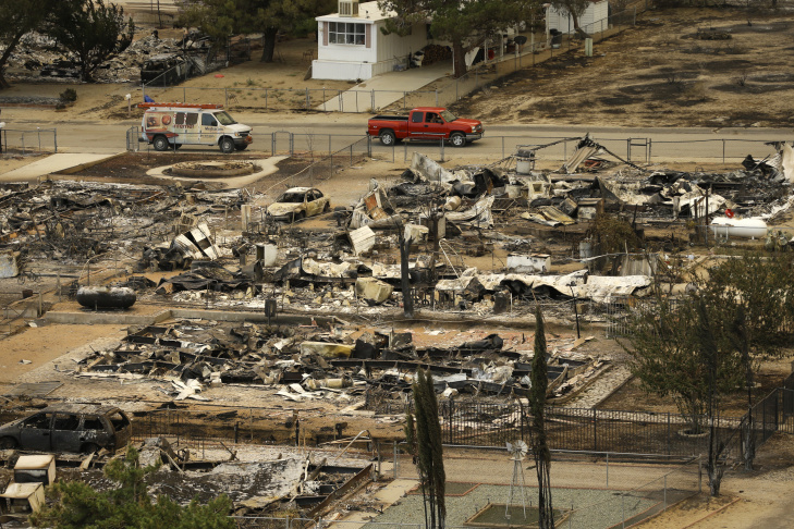 A pickup truck passes by the remains of mobile homes devastated by a wildfire, Saturday, June 25, 2016, in South Lake, Calif.
