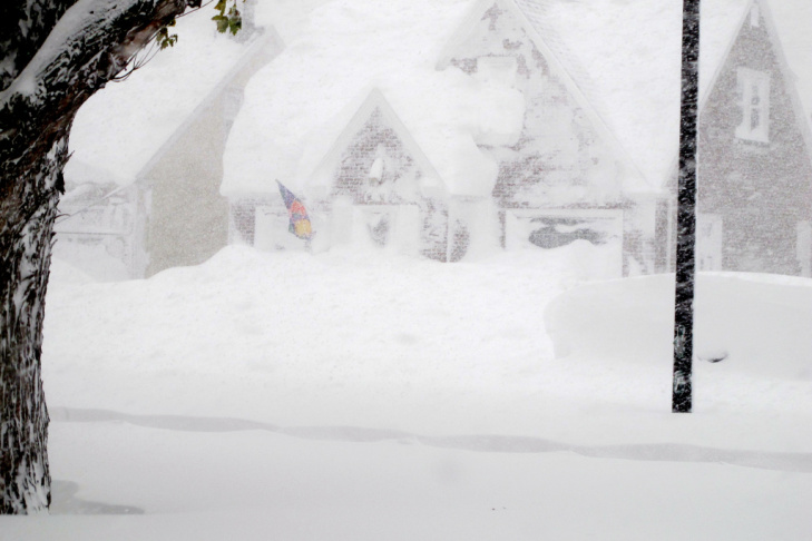 A house is obscured by wind-blown, lake-effect snow on Tuesday.