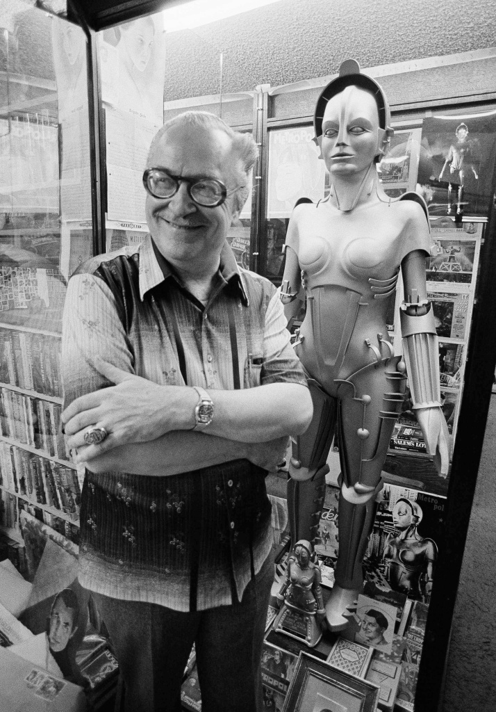 """Mr. Science Fiction"", Forrest Ackerman, stands with the reproduction of the female robot Ultima Future Automation from the 1926 German film ""Metropolis"" in his home in Los Angeles, on Oct. 31, 1979. The robot is surrounded by Ackerman's extensive collection of science fiction and fantasy memorabilia."