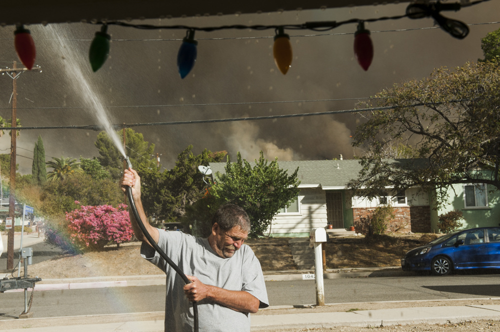 Dan Anctil sprays water on his roof near the edge of the Creek Fire in Lakeview Terrace on Dec. 5, 2017.