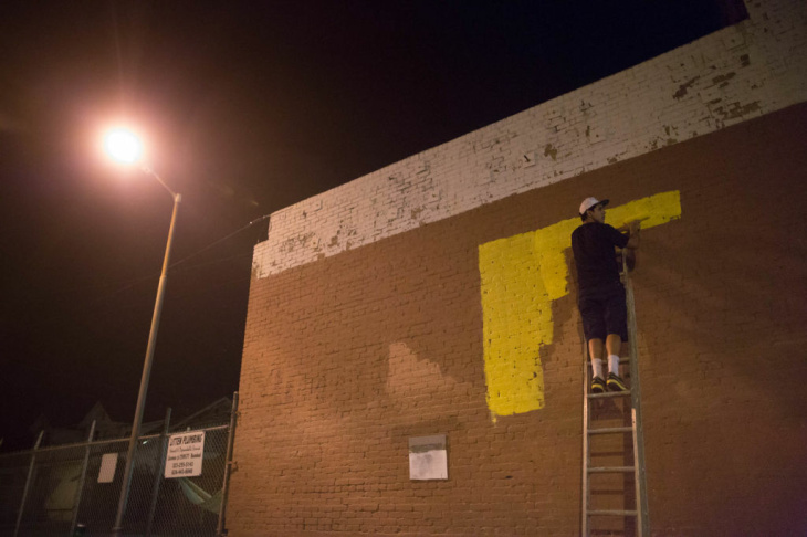 Graffiti Artist Edward Mompeller works on a mural on the side of Michael Kosman's Triumph Optical shop in Highland Park.