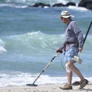 A man uses a metal detector while search