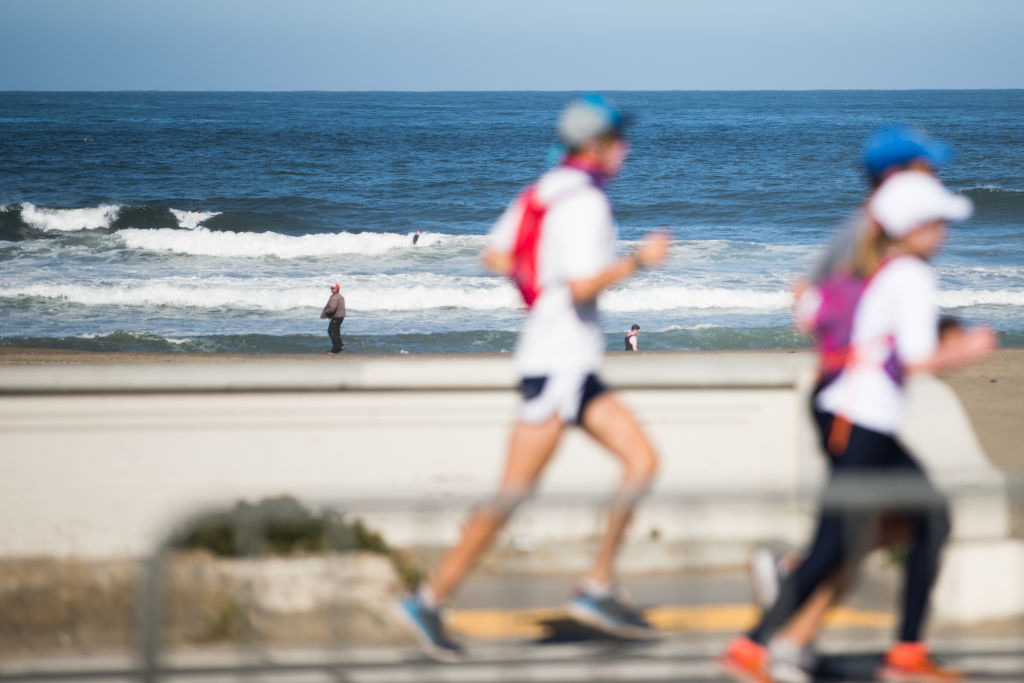 People run on a beach path during the coronavirus pandemic on May 03, 2020 in San Francisco, California.