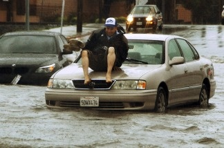 A man gets ready to jump off the hood of his car, stalled on flooded Vineland Ave between Vanowen and Sherman Way in the North Hollywood area of Los Angeles' San Fernando Valley on March 20, 2011. The first day of spring arrived with a bang in Southern California, bringing heavy snow to the mountains and illuminating the sky with flashes of lightning from Santa Barbara to downtown Los Angeles.