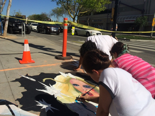 Artists from We Talk Chalk create a 3D street painting on the corner of Santa Monica Blvd and Westmount Dr in West Hollywood. The image is designed to catch people's attention before crossing the street so they aren't on their phones.