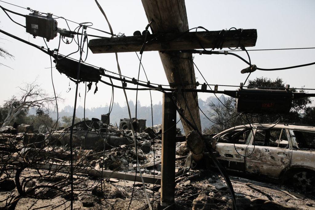 A downed power line and the remins of a home and a car are seen in the Larkfield-Wikiup neighborhood following the damage caused by the Tubbs Fire on October 13, 2017 in Santa Rosa, California.