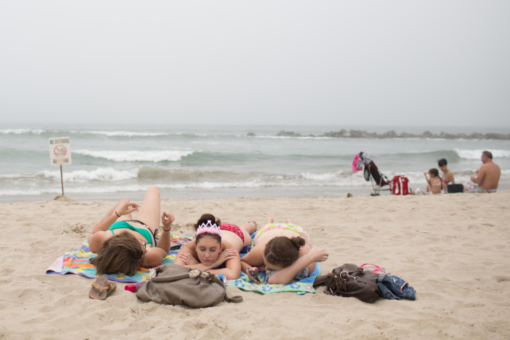 Girls take a nap at Venice Beach on June 27th, 2013. Temperatures at Venice Beach will be cooler than inland areas in Los Angeles this weekend.