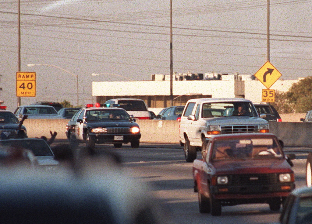 Motorists wave as police cars pursue the Ford Bronco (white, R) driven by Al Cowlings, carrying fugitive murder suspect O.J. Simpson, on a 90-minute slow-speed car chase June 17, 1994 on the 405 Freeway in Los Angeles.