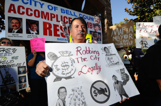 Mario Sanchez, a resident of the City of Bell, holds a protest placard calling for the ouster of city officials before the start of a council meeting on July 26, 2010 in Bell, California.