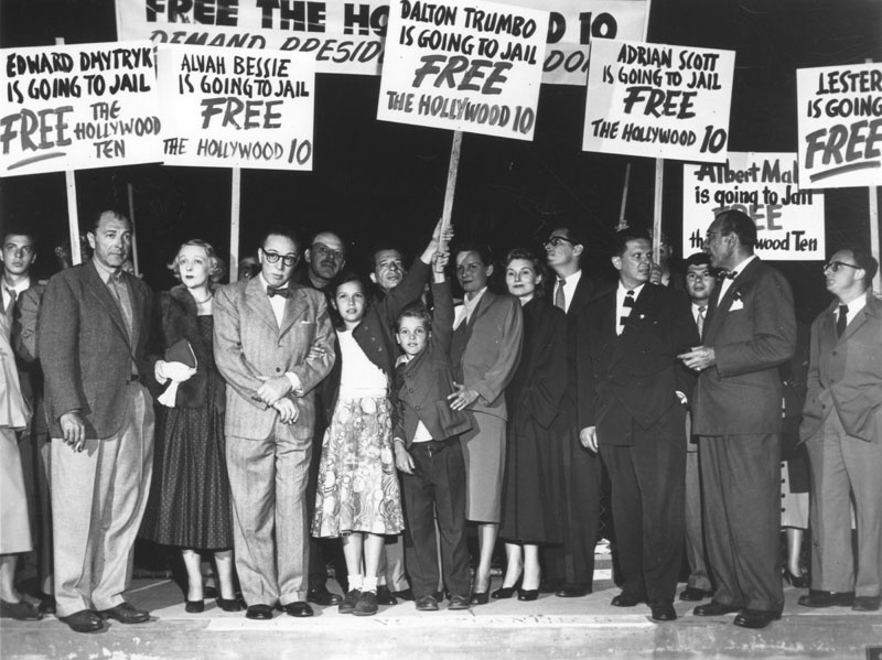 The Hollywood Ten were writers convicted of contempt of Congress for refusing to answer questions by the House Committee on Un-American Activities in Washington, D.C. in the fall of 1947. Here, staging a demonstration at the LA Airport with families and attorneys, are: Lester Cole, Dalton Trumbo, Alvah Bessie, Nicole Trumbo, Christopher Trumbo, Cleo Trumbo, Mrs. Ring Lardner, Jr., Ring Lardner, Jr., Ben Margolis (attorney for the 10), and Herbert Biberman.