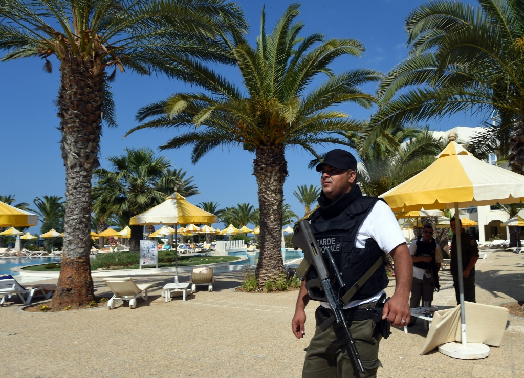 A Tunisian security member stands next to a swimming pool at the resort town of Sousse, a popular tourist destination 140 kilometres (90 miles) south of the Tunisian capital, on June 26, 2015, following a shooting attack. At least 27 people, including foreigners, were killed in a mass shooting at a Tunisian beach resort packed with holidaymakers, in the North African country's worst attack in recent history.