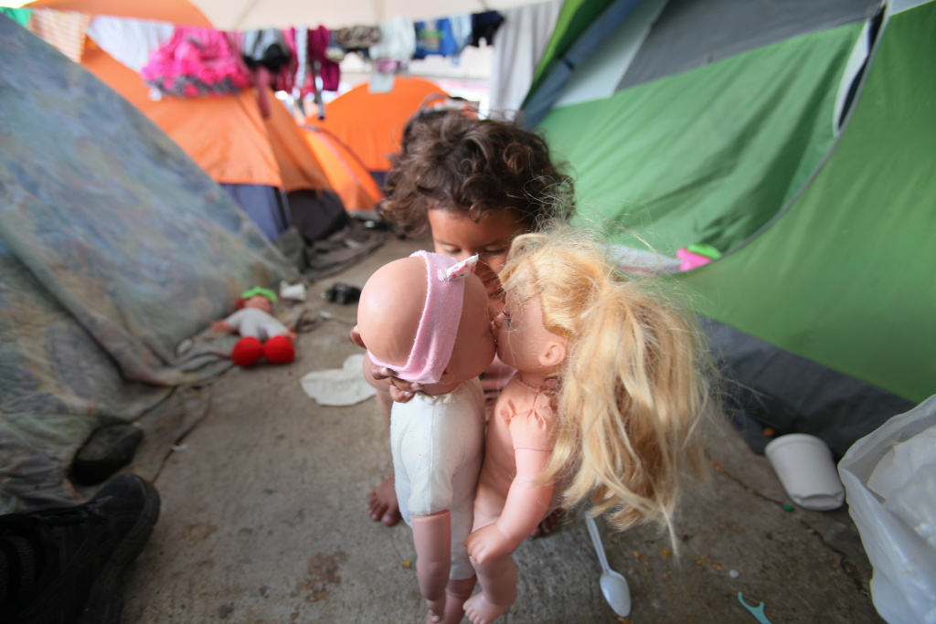 At the El Barretal shelter in Matamoros, Tijuana, Monserrat Reyes, 3, has her new dolls kiss, as she plays near her family's tents with the toys she was given on Dec. 16, 2018.