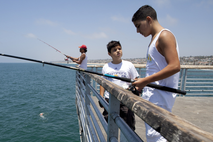 Paul Manasefi, 12, center, talks with John Zein, 13, as they fish on the Hermosa Beach Pier. Fishing is now prohibited at the Manhattan Beach Pier until Sept. 7 after a swimming was attacked by a juvenile great white shark caught on a fishing line.