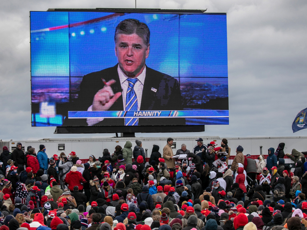 Supporters of President Trump watch a video featuring Fox News host Sean Hannity ahead of Trump's arrival for a campaign rally Friday in Waterford Township, Mich.
