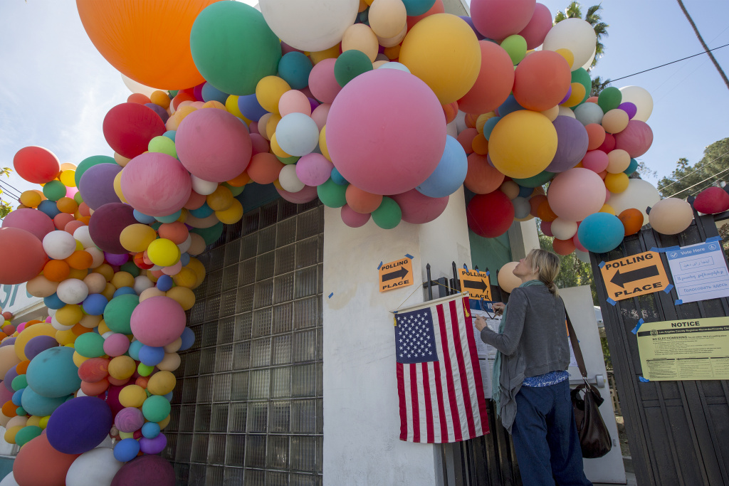 A woman looks at balloons covering a polling place at the Hollywood Sunset Free Clinic in the Silver Lake area of Los Angeles as voters went to the polls on March 7, 2017.