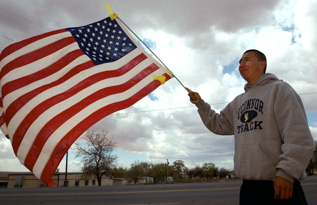 Ponyson Begay waves a flag adorned with yellow ribbons while walking down Main Street on the Navajo Indian Reservation April 5, 2003 in Tuba City, Arizona.
