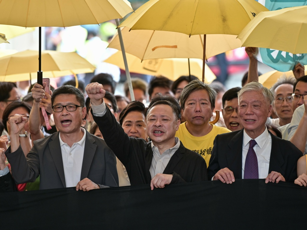 Sociology professor Chan Kin-man (left), law professor Benny Tai (center), and Baptist minister Chu Yiu-ming (right) chant slogans before entering the West Kowloon Magistrates Court in Hong Kong on Wednesday to receive their sentences after being convicted on