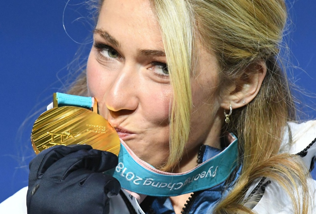 Team USA's Mikaela Shiffrin kisses her gold medal on the podium during the medal ceremony for the women's alpine skiing giant slalom at the 2018 Pyeongchang Winter Olympics.