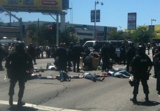 Los Angeles Police Department officers use cutting devices to free protesters who had linked their arms together at the corner of Wilshire Boulevard and Highland Avenue in L.A.