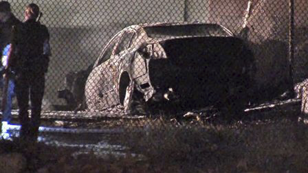 This image taken from video provided by ABC-TV shows officials at the site of a fiery single-vehicle crash Saturday Sept. 28, 2013 that killed 5 people in Burbank. There was one survivor found about 50 yards from the burning Nissan when police arrived on the scene around 4 a.m. Officials said speed appeared to be a factor in the crash.