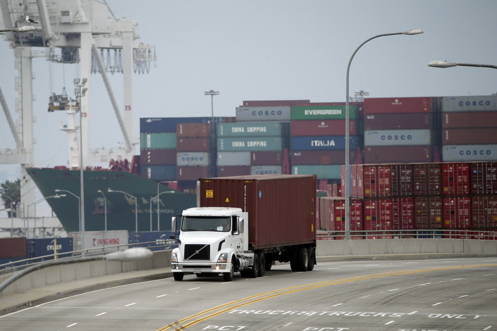 A truck with a shipping container leave the Port of Long Beach, Tuesday, Feb. 17, 2015, in Long Beach, Calif. Seaports in the U.S. West Coast that were all but shut over the weekend because of a contract dispute are reopening as the nation's top labor official tries to solve a stalemate between dockworkers and their employers that already has disrupted billions of dollars in U.S. international trade. (AP Photo/Jae C. Hong)