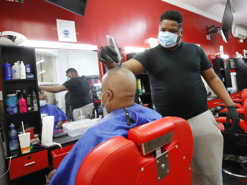 Wilkin Soto works on a customer at the Castillo Barbershop, in Lawrence, Mass., on June 5.