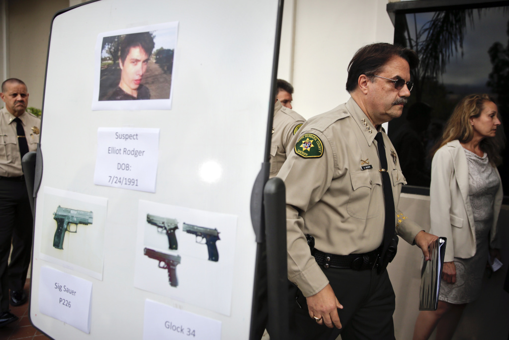 Santa Barbara County Sheriff Bill Brown, right, walks past a board showing photos of suspected gunman Elliot Rodger and the guns he used in the Isla Vista shootings.
