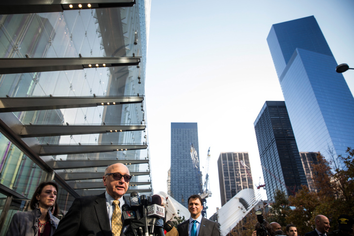 Laborers (C) use a lift as they work at the transportation hub of the One World Trade Center in New York on October 17, 2014. On Monday, November 3, 2014, the building opened for business. Officials say it is currently at 60% occupancy, with Conde Nast as one of the first major tenants to move in.