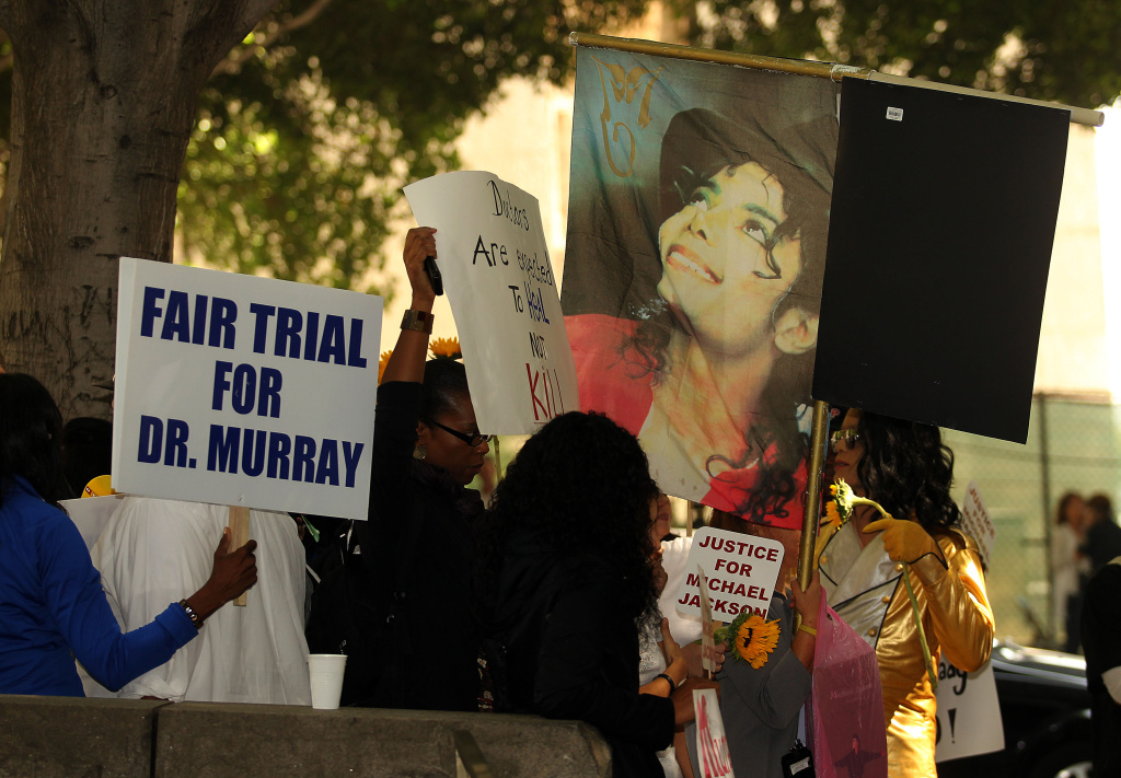 Demonstrators hold signs outside the Los Angeles Courthouse during opening statements for the trial of Dr. Conrad Murray.