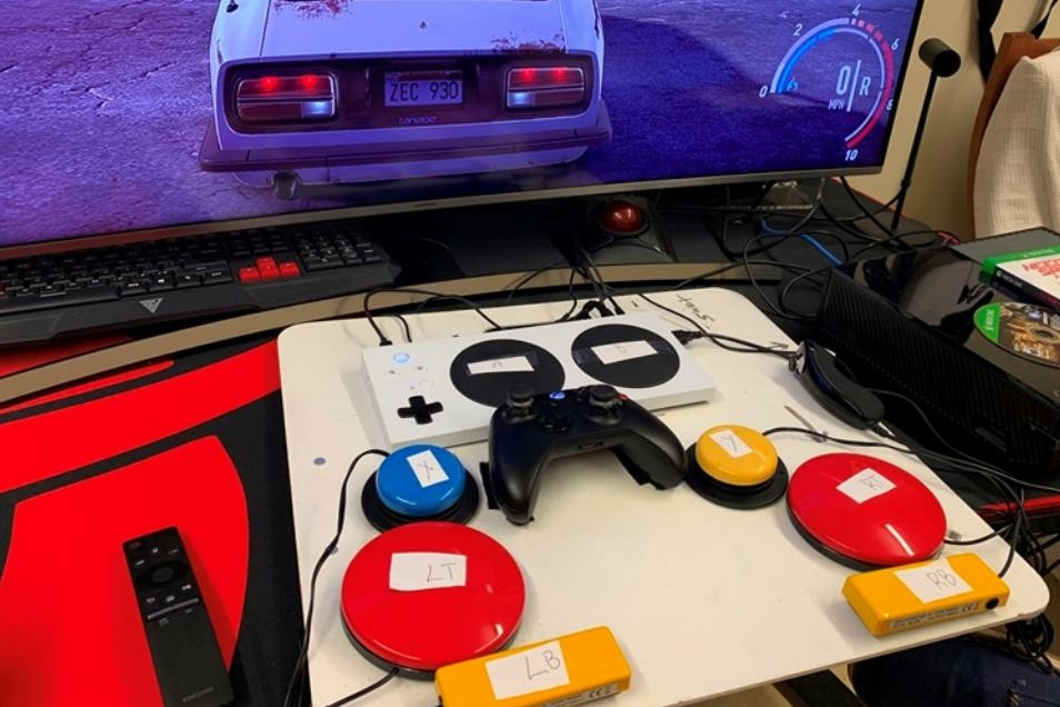 The white rectangular Xbox adaptive controller can be paired with attachments such as the colored buttons to assist people with a variety of injuries.