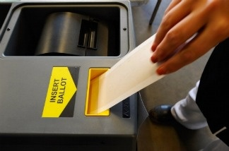 A voter places her ballot into a ballot box in Los Angeles, California.