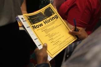 A job seeker reads a flier at a state-sponsored job fair in Denver, Colorado. The House of Representatives has just failed to pass an extension of unemployment benefits.