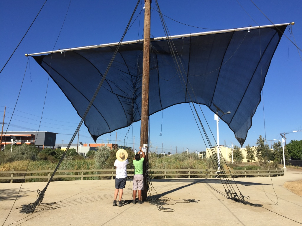 Artists Joshua Callaghan, left, and Daveed Kapoor, right, raise the sails on their sculpture, Mast, on July 15, 2016. The sculpture is part of LA's first public art biennial, CURRENT:LA, and is located in South LA Wetlands Park.