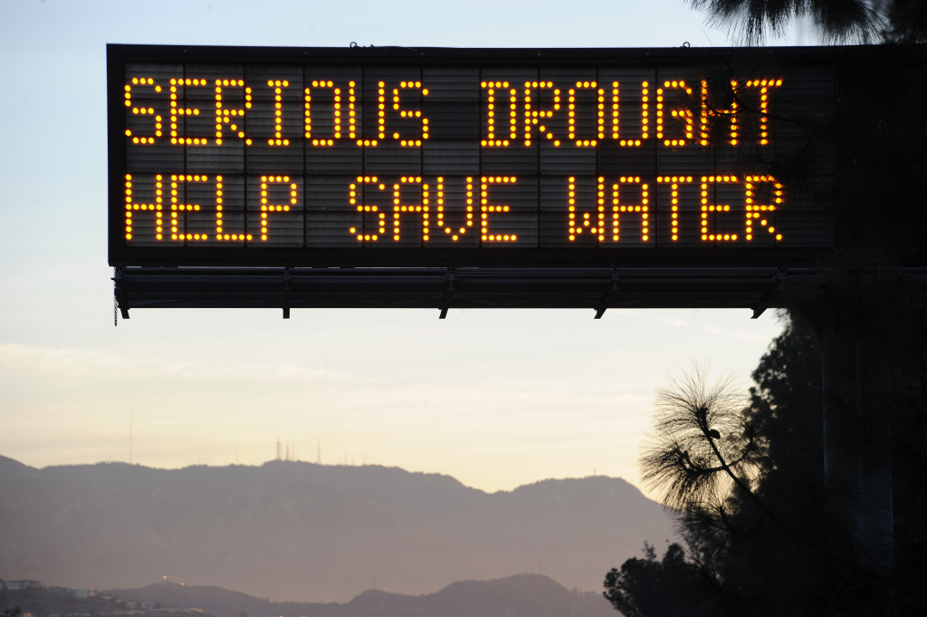 A sign displays the message to help conserve water.
