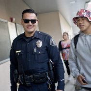 Los Angeles School Police Officer Nick Flores walks with students at Valley Academy of Arts and Sciences as school gets out on Wednesday, Dec. 10, 2014.