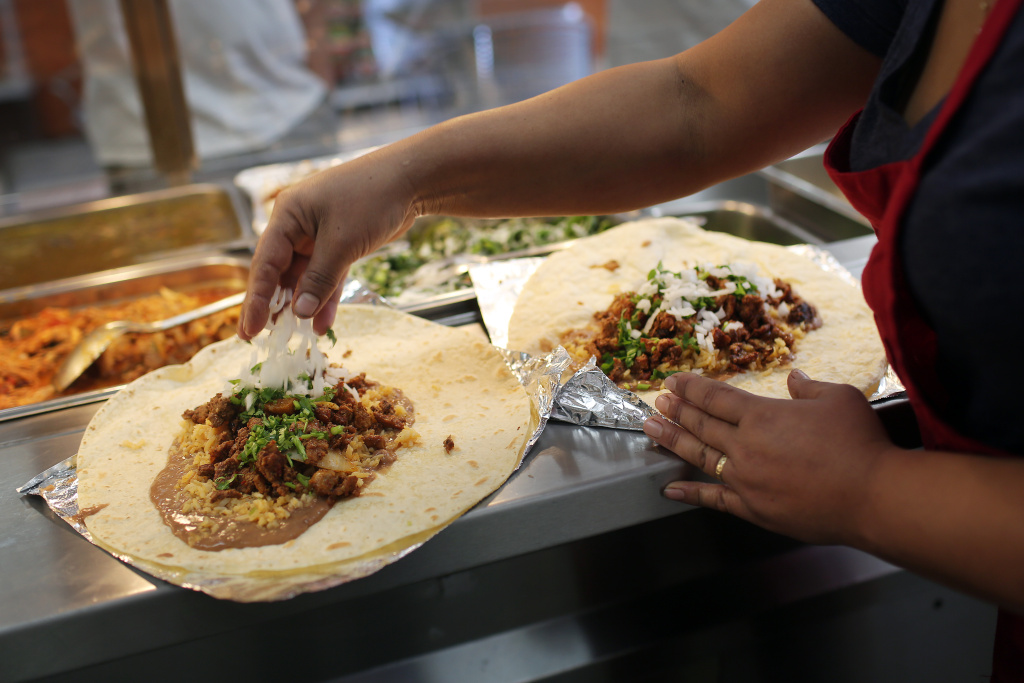 Poncitlan cook Enedina Arrellano sprinkles chopped onions on two burritos. In the last year, the store owner shifted to focus on being a burrito shop.