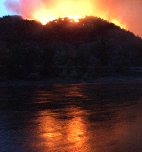 June 8: Flames from the Hayman wildfire, burning in in the Rocky Mountains southwest of Denver, reflect on the Colorado River.