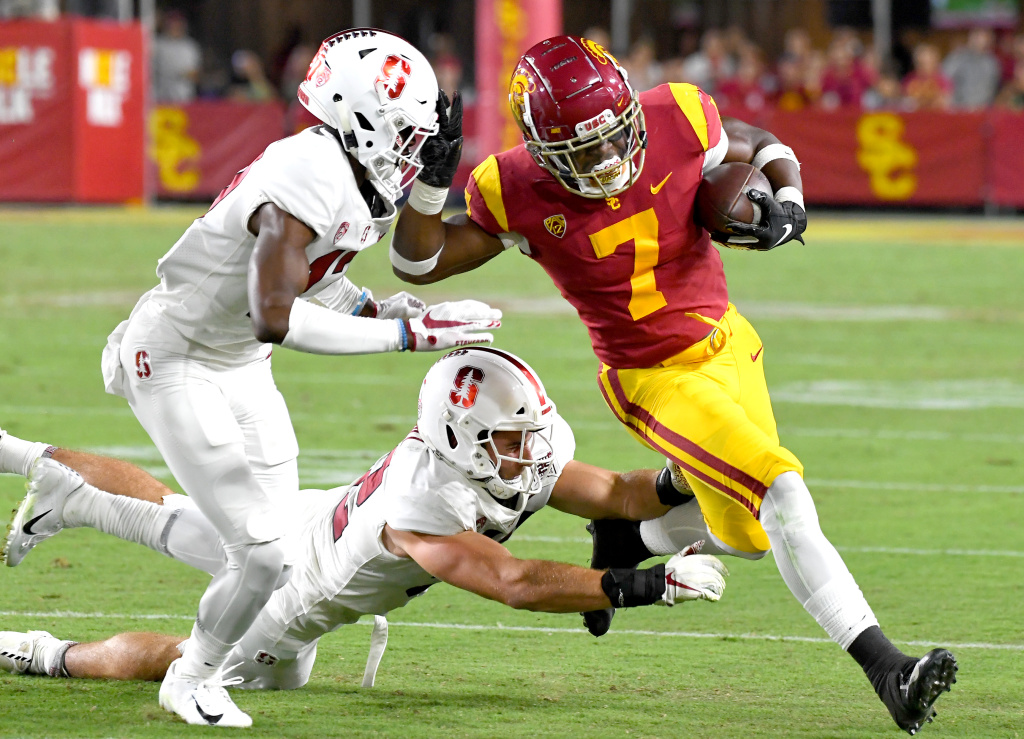 Running back Stephen Carr #7 of the USC Trojans breaks away from linebacker Casey Toohill #52 and cornerback Kyu Blu Kelly #17 of the Stanford Cardinal on September 7, 2019 in Los Angeles, California.
