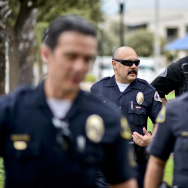 Anaheim Community Policing Team Officer Jesse Romero, center, walks with colleagues in the Guinida Lane neighborhood in Anaheim Thursday.
