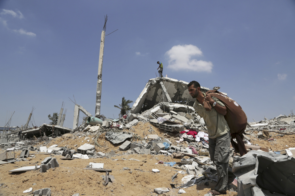 A Palestinian carries belongings he collected from rubble of his destroyed home hit by an Israeli strike in Khuzaa, east of Khan Younis, in the northern Gaza Strip, Tuesday, Aug. 5, 2014. Israel and Hamas began observing a temporary cease-fire on Tuesday that sets the stage for talks in Egypt on a broader deal on the Gaza Strip, including a sustainable truce and the rebuilding of the battered, blockaded coastal territory.