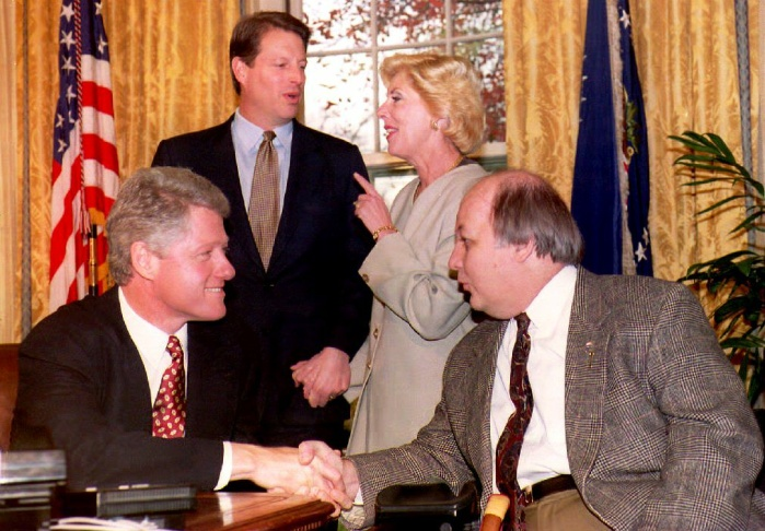 File photo: U.S. President Bill Clinton (L) congratulates former Reagan Administration Press Secretary James Brady (R) on the passage of the Brady bill as Vice President Al Gore (2nd-L) and Sarah Brady look on during a meeting at the White House 24 November 1993. The bill will require a five-day waiting period and background check on handgun buyers.