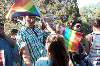 Mark Hiebert holds his 4-year-old son, Logan, while his 6-year-old daughter Amira waves a rainbow flag at West Hollywood Park.