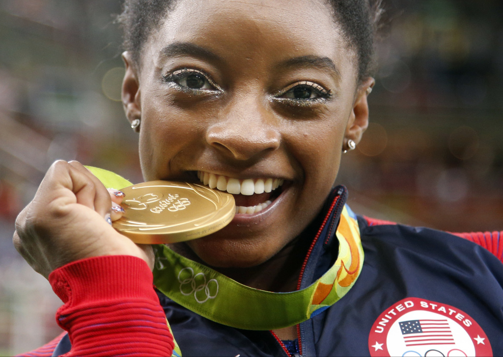 United States' Simone Biles bites her gold medal for the artistic gymnastics women's individual all-around final at the 2016 Summer Olympics in Rio de Janeiro, Brazil, Thursday, Aug. 11, 2016. (AP Photo/Dmitri Lovetsky)