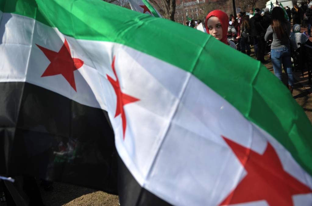 File photo: A woman is seen behind a Syrian opposition flag during a rally against the Syrian government on March 15, 2014 at Lafayette Square, across from the White House, in Washington to mark the third anniversary of the start of the conflict in Syria.