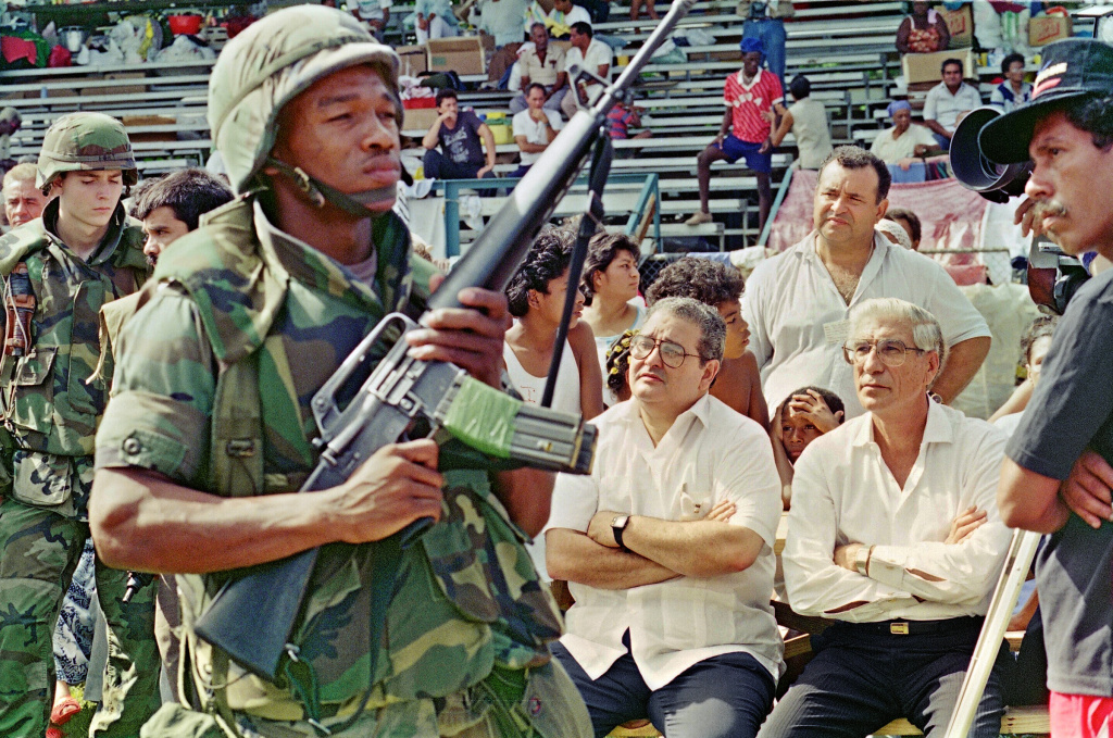 A US soldier guards the newly installed Panamian leaders President Guillermo Endara (C) and vice-president Guillermo Ford (R) at a refugee center Christmas ceremony 25 December 1989 in Panama City.