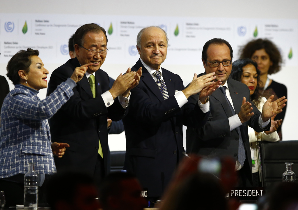 French President Francois Hollande, right, French Foreign Minister and president of the COP21 Laurent Fabius, second, right, United Nations climate chief Christiana Figueres and United Nations Secretary General Ban ki-Moon applaud after the final conference on climate change in Le Bourget, north of Paris.
