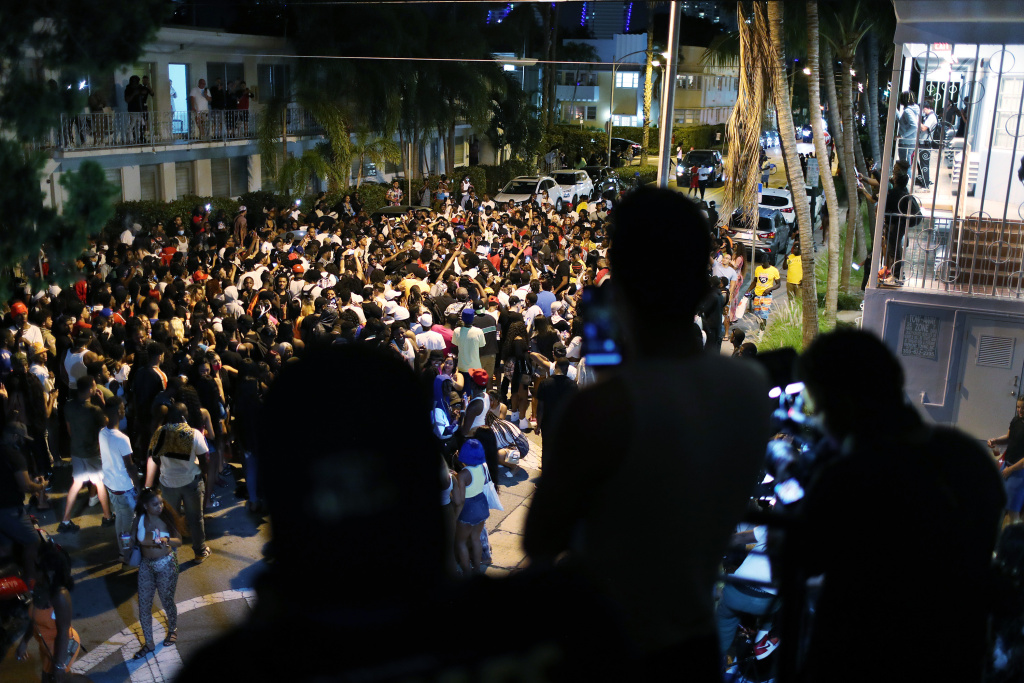 People gather while exiting the area as an 8pm curfew goes into effect on March 21, 2021 in Miami Beach, Florida.