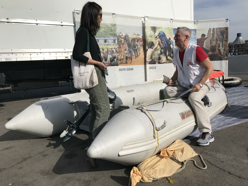 John Fiddler speaks with KPCC's Josie Huang at the boat that's meant to represent how displaced people would flee war-torn countries by sea. Fiddler says this boat would be a more luxurious example