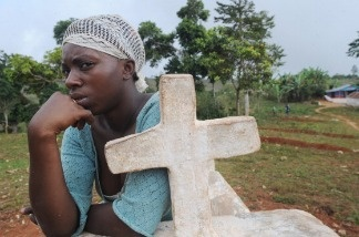 A Haitian woman sits by a cross January 10, 2011 in Duvillon.